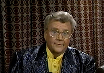 Rod is wearing a gold jacket with black dots and black lapels & white silk collarless shirt