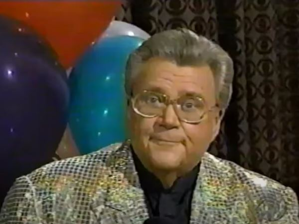 Rod is wearing a gold sequined jacket & black collarless silk shirt