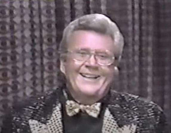 Rod is wearing a black sequined jacket with gold lapels (and black sequins), gold bow tie & a black shirt